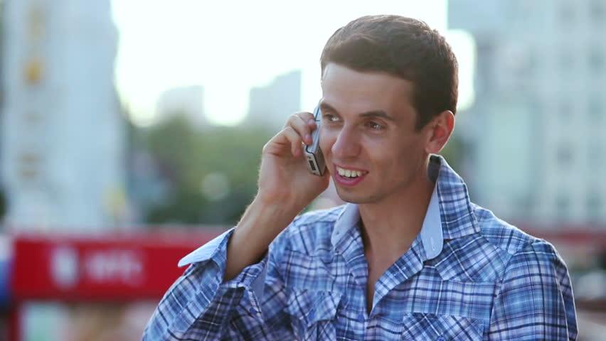 Man talking over phone smiling enjoying call conversation, city