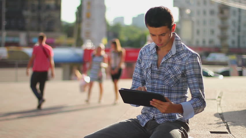 Young business man reading tablet pc computer on city square