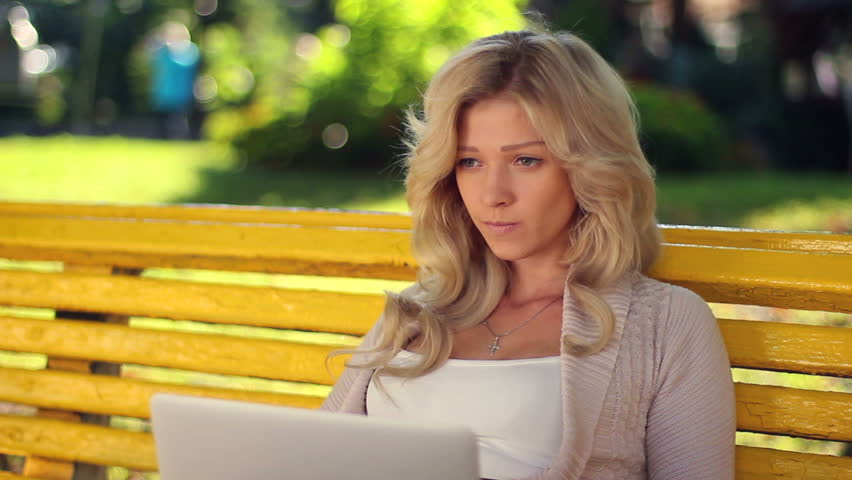 Young female reads message laptop smiles chatting social network