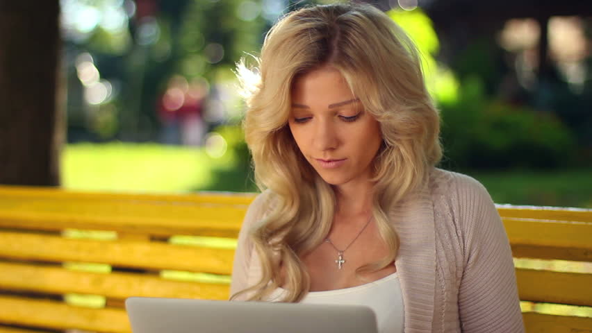 Young woman typing message in laptop smiling closeup, park bench