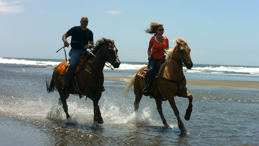 Couple riding horses on beach, slow motion