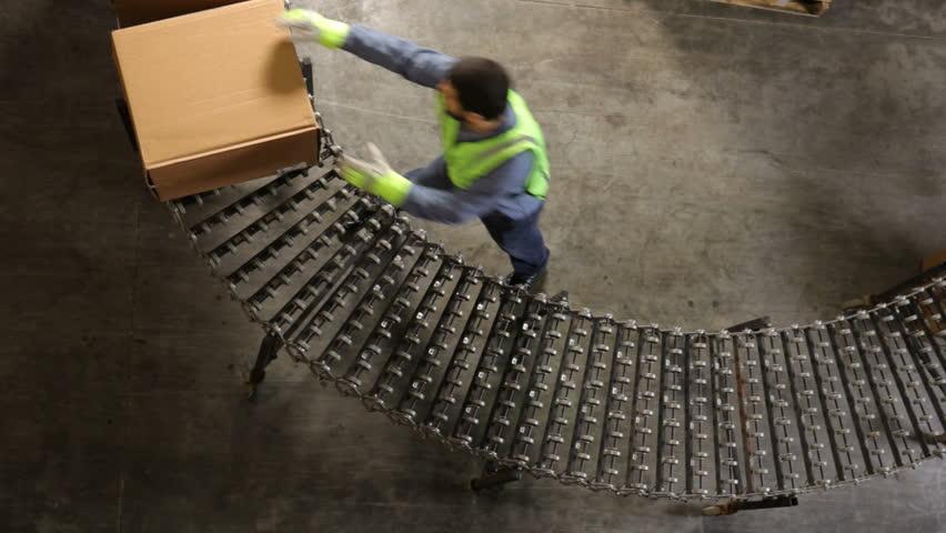 Man in shipping warehouse moves boxes along conveyor