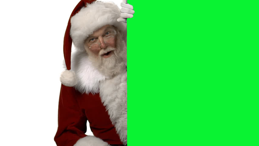 Santa reveals himself from behind a green screen box, looks into the camera smiles and puts his finger to his lips to shush