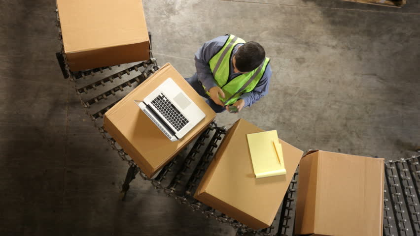 Man in shipping warehouse uses laptop, overhead view