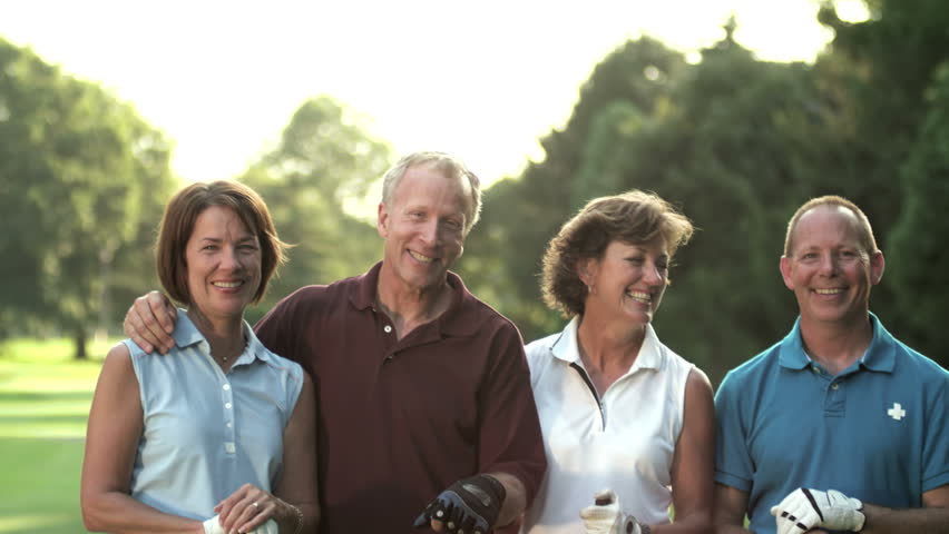 Baby boomer golfers stand and smile at the cameras. Medium shot.