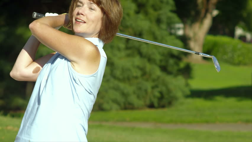 Baby boomer golfer is pleased with her shot from a sand pit. Medium shot.