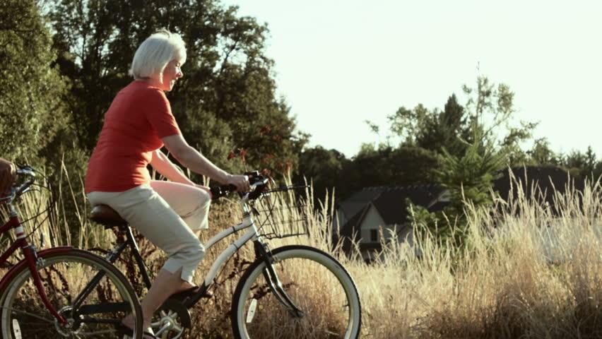 Happy couple take a bike ride together down a side walk. Wide shot.