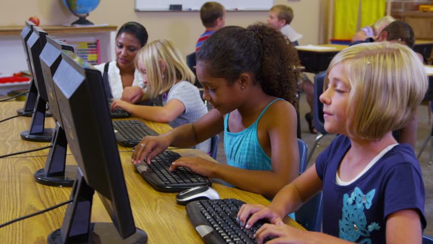 Elementary school teacher helps students with computers   Shutterstock HD Video #4696520