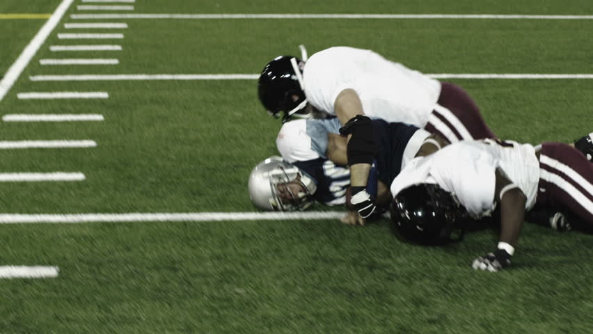 Close up of a football running back getting tackled by two defenders