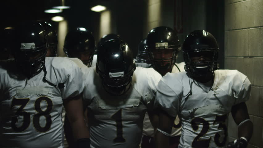 Football team walks down a dark tunnel towards the field before a game | Shutterstock Video #4706294