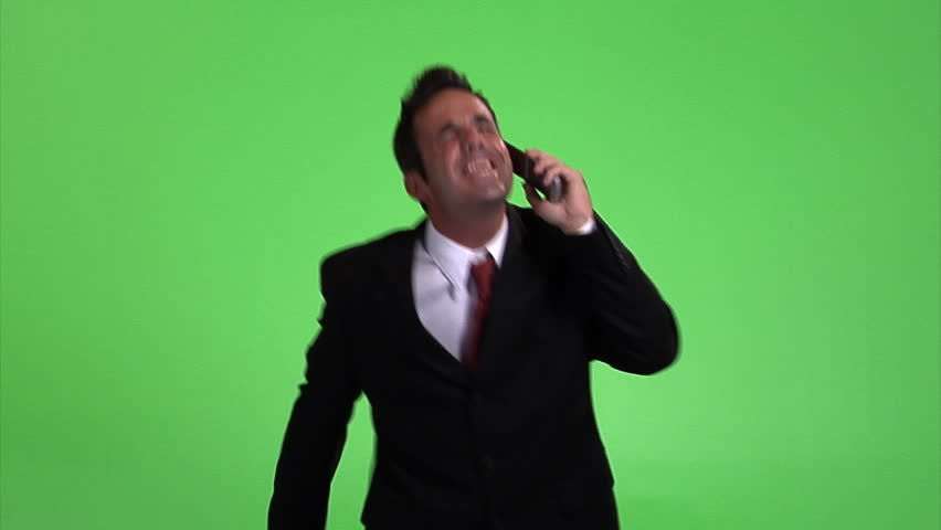 Excited businessman with cell phone dancing against green screen