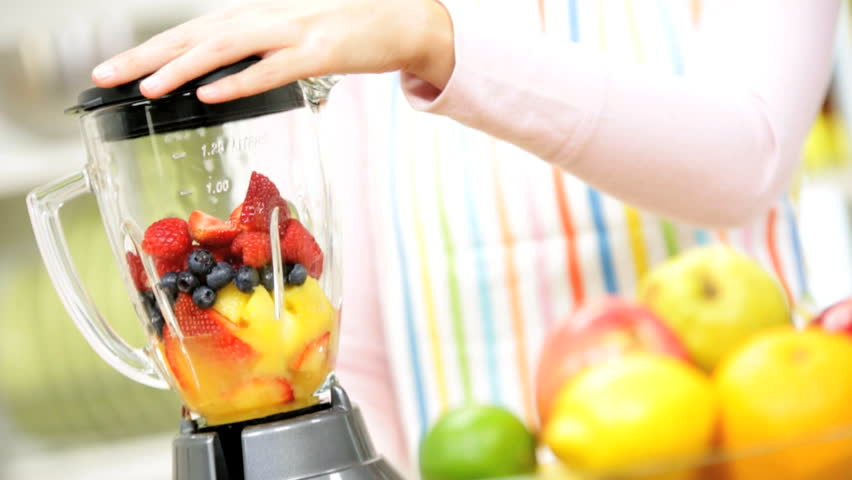 Caucasian girl makes nutritious fresh homemade fruit smoothie with electric blender