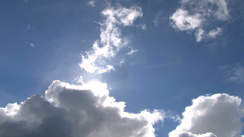 Time lapse of cloudscape with bright sun shining and revealing itself behind
