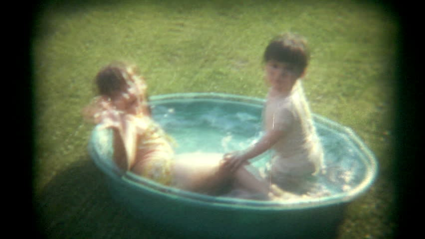 A brother and sister play in a baby pool outside.   Vintage 1970s film transfer.