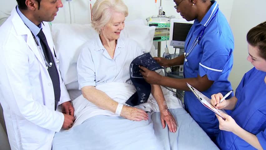 Elderly female patient having blood pressure taken at bedside by multi ethnic medical team   Shutterstock HD Video #4761476
