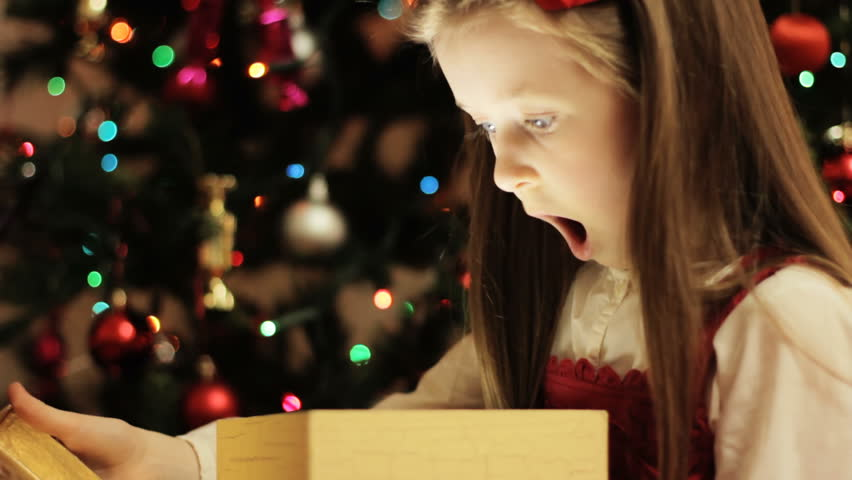 Christmas gift surprise - A little girl opens a Christmas present in amazement | Shutterstock HD Video #4766759