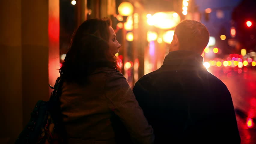 A couple walks away from the camera at night while walking the city streets with lots of lights in the background