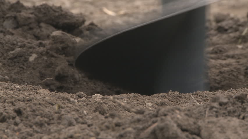 A very close view of an auger digging a hole for a post