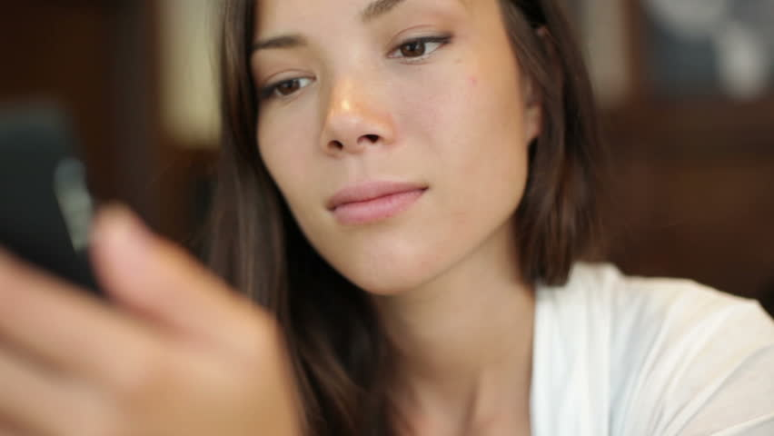 Woman using app on smartphone in cafe drinking coffee smiling and texting on mobile phone. Beautiful multicultural young casual female professional on mobile phone. Mixed race Asian Caucasian model.