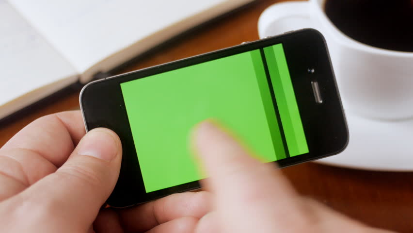 Man looking through green screen pages on smartphone