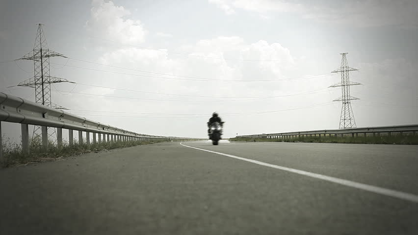 Man sitting on the motorcycle and moving on the road.
