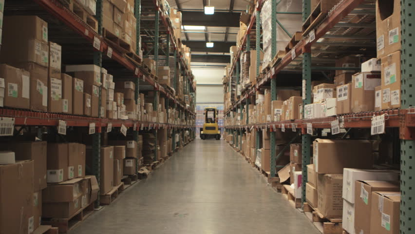 Camera cranes up on shelves of cardboard boxes inside a storage warehouse.
