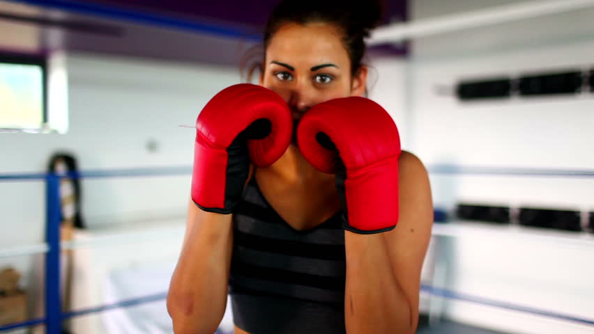 Aggressive fit woman wearing red boxing gloves boxing looking at camera
