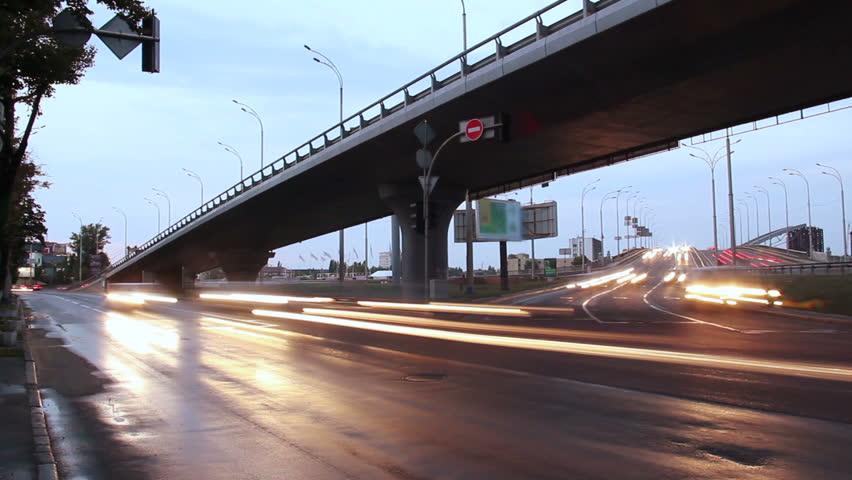 City traffic road junction, bridge highway, car lights turned on