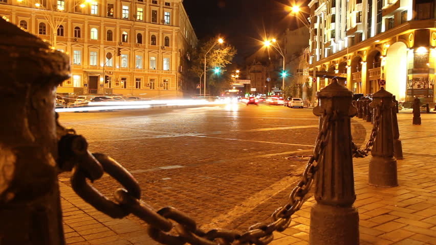 Evening city street, cars drive, yellow red lights, chains posts