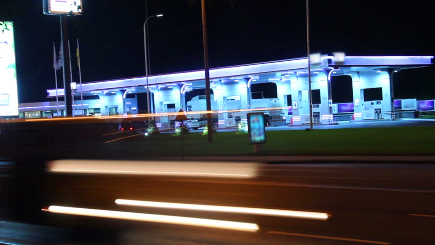 Fueling station night view timelapse, car leave red light traces