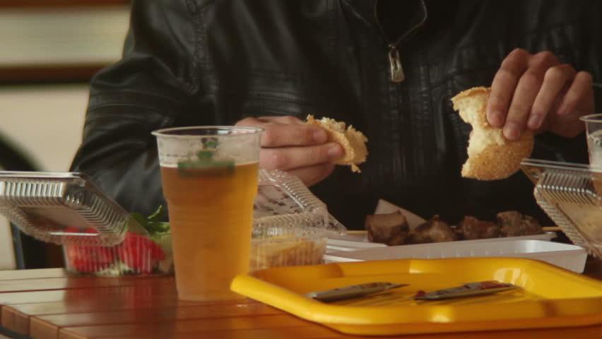 Man eating fast food restaurant meal, burgers meat beer, dining