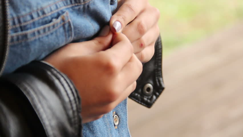 Woman hands getting buttons done on jeans shirt, undone