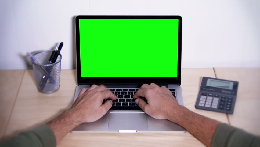 A man types on a laptop on his desk.  Green screen for your custom screen