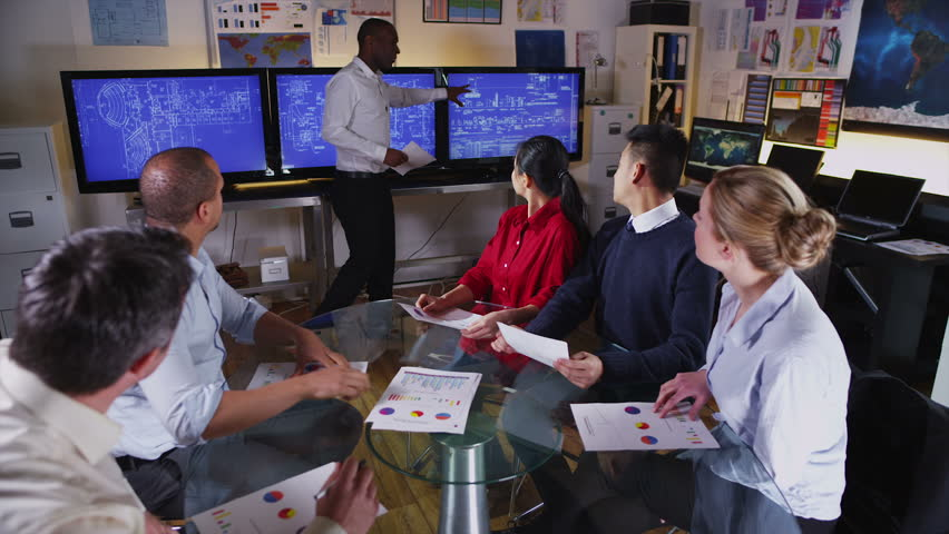 attractive black businessman giving a presentation or training session to his colleagues and using three large - Fashion Designer Education And Training