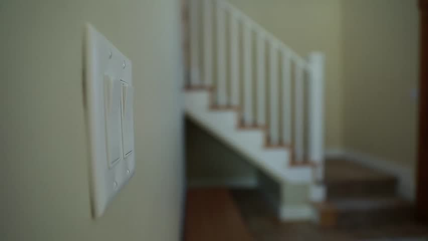 A man turns on a light switch and then walks upstairs in his home