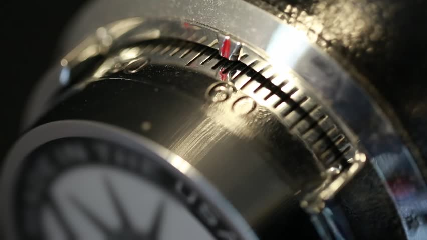 A hand opens a combination lock on a steel vault
