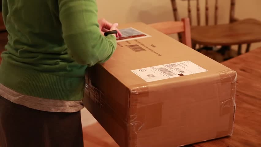 A woman opens a package that she received in the mail