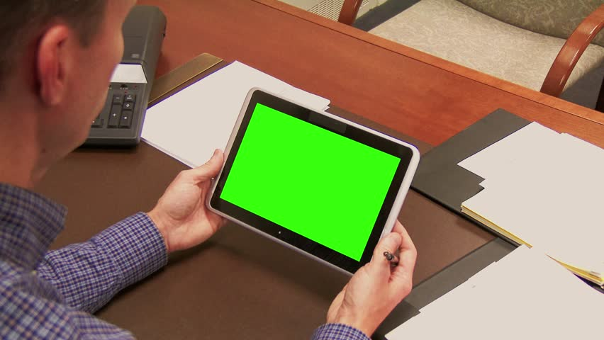 A finance officer works at his desk with a tablet PC. Green screen tablet for