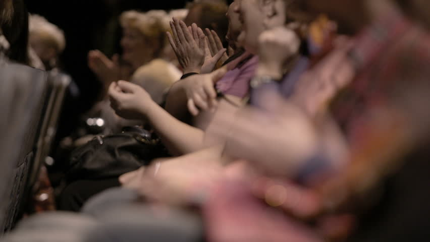 Impressed audience, made of Caucasian people sitting down, applauding, during a spectacular event. Close up hands only with no faces. Focus goes from back to front. #5249192