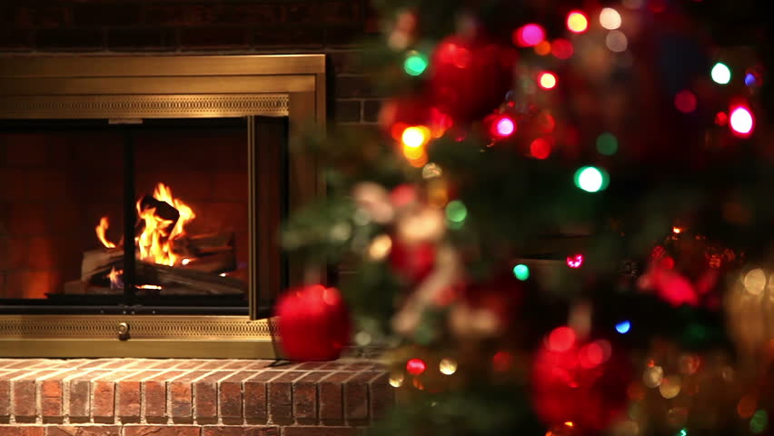 Static Shot of a Fire Burning in a Brick Fireplace with an Out of Focus Decorated Christmas Tree in the Foreground. Focus Changes to the Christmas Tree.