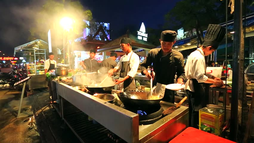 SIEM REAP, CAMBODIA - CIRCA DECEMBER: Pub Street, chef cook a meal at
