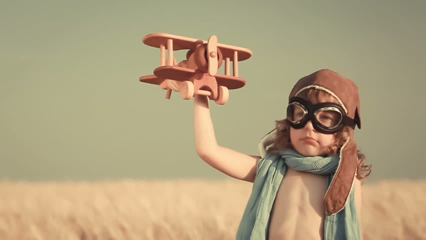Happy kid playing with toy airplane against summer sky background | Shutterstock Video #5541338