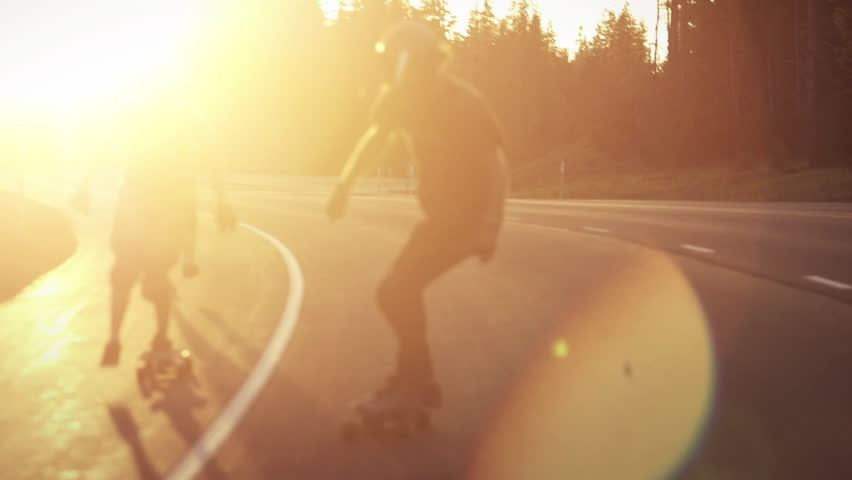 Skateboarders bomb hill during sunset in slowmotion | Shutterstock HD Video #5543789