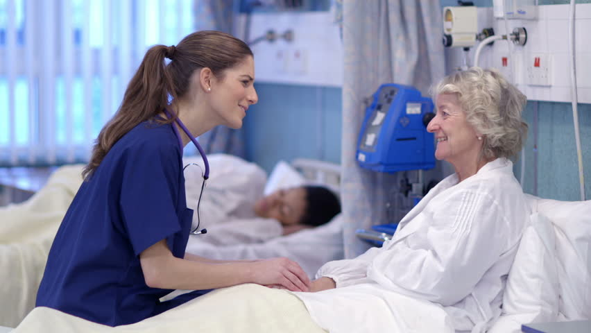 Caring nurse chats with an elderly female patient on a hospital ward.   Shutterstock HD Video #5784089