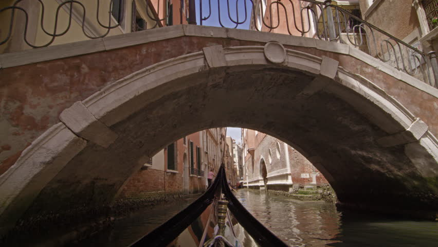 View from a gondola as it glides under a bridge in canal