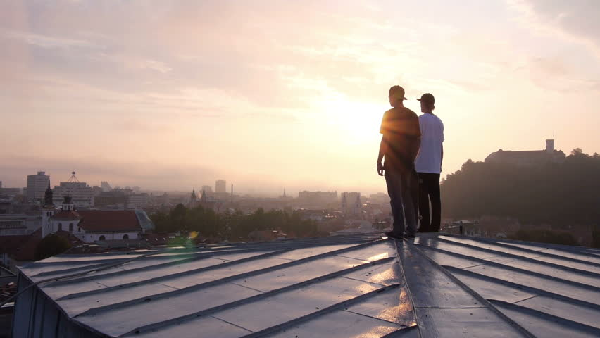 AERIAL: Two young skateboarders standing on rooftop | Shutterstock Video #5807138