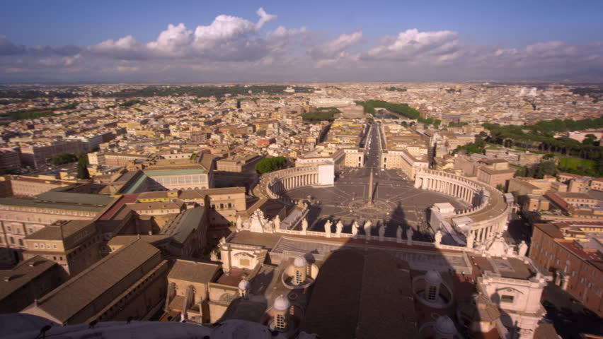 Aerial pan of St Peter's plaza and the rooftops of Rome