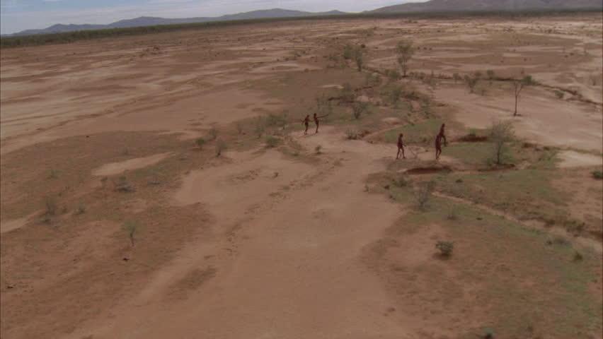 aborigines walk across red sand