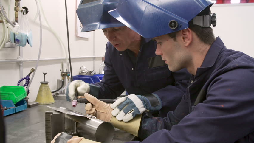 Engineer Explaining To Female Apprentice How To Use TIG Welding ...