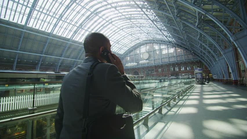 Businessman makes a phone call as he walks...